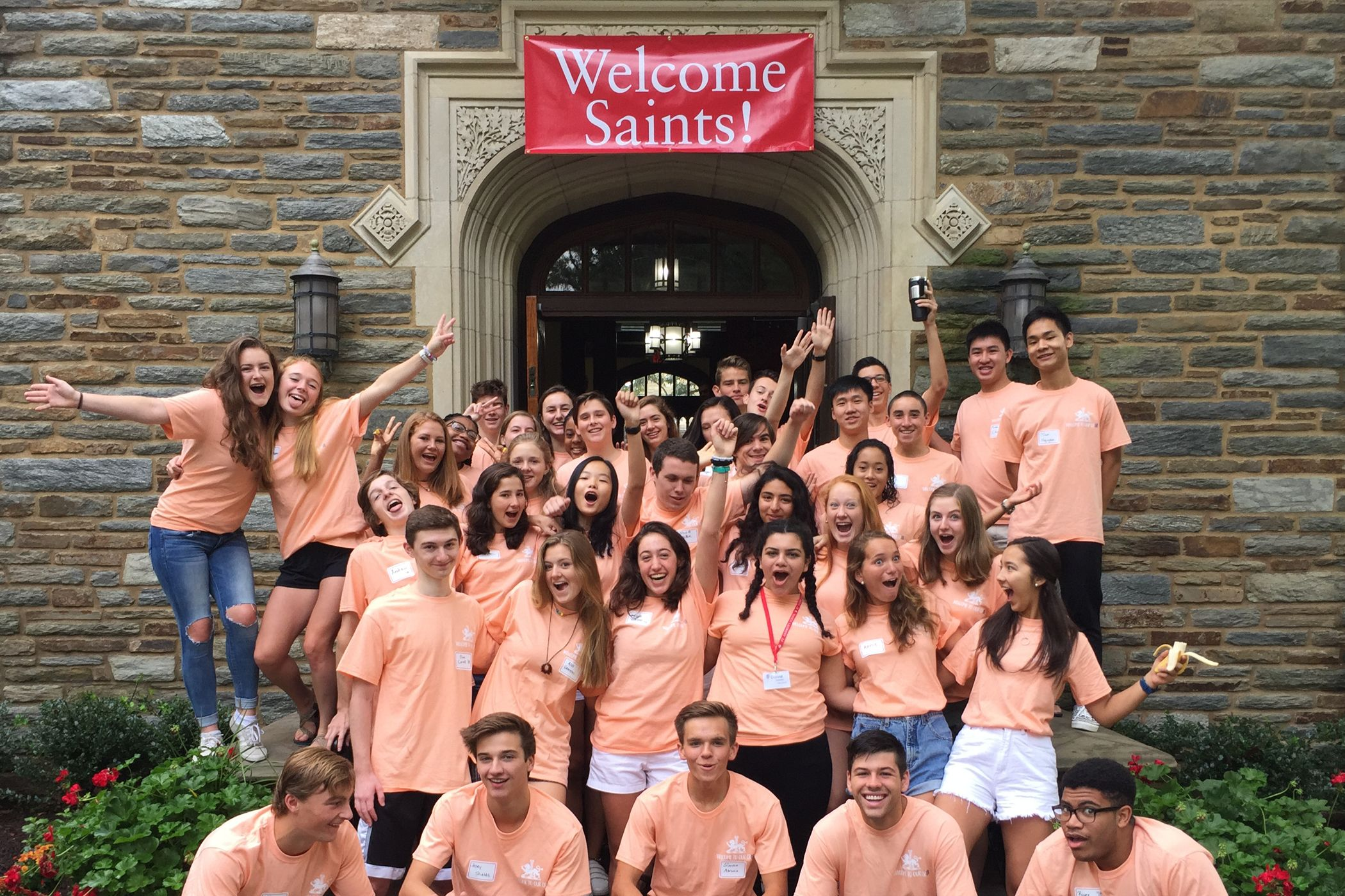 Students with Welcome Saints banner